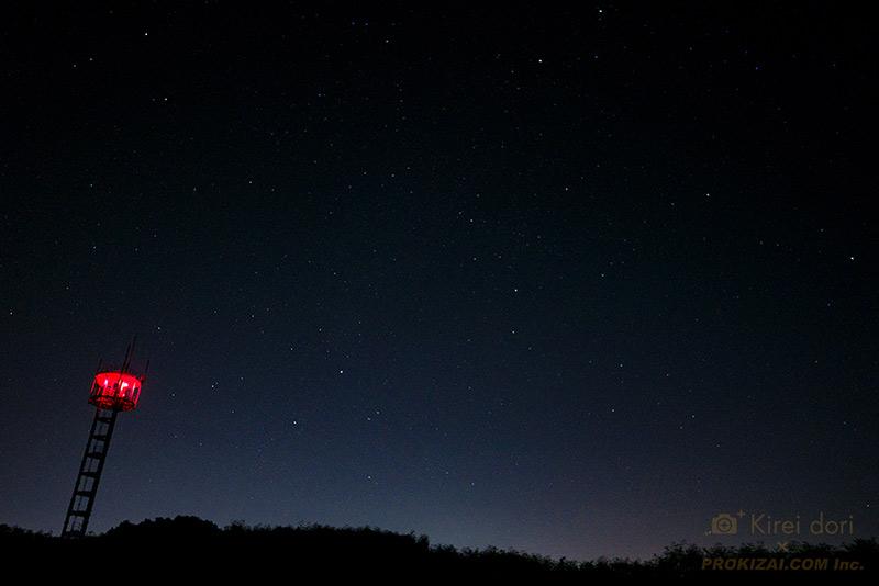 人工物や町明かりと山と星空の写真
